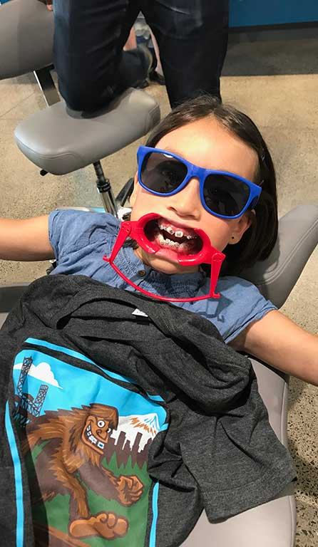A girl in dental chair with Sasquatch shirt in her lap at Senestraro Family Orthodontics