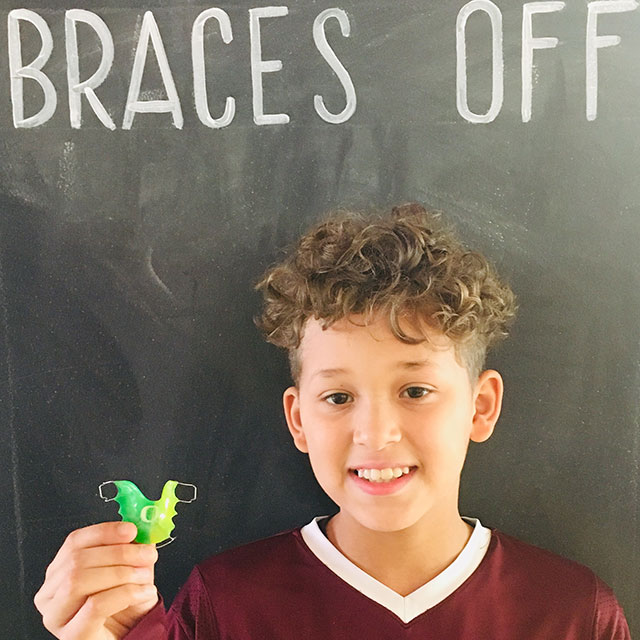 A young patient poses with a retainer in front of our 'Braces Off' chalkboard